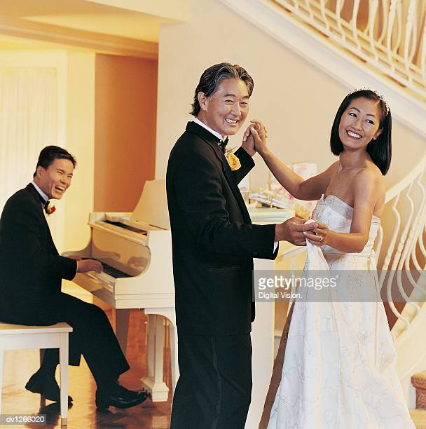 Newlywed Couple Dancing With a Man Playing the Grand Piano in the Background