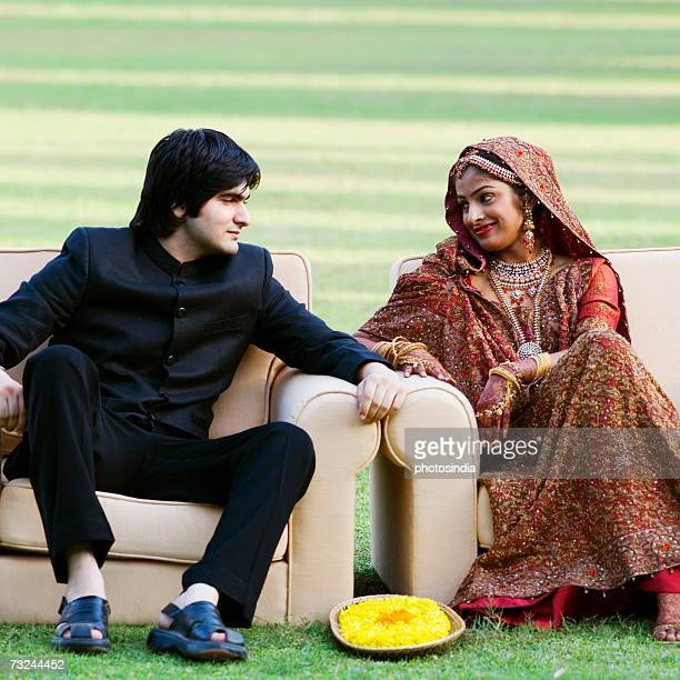 Newlywed couple in traditional wedding dress sitting in armchairs in a lawn and looking at each other
