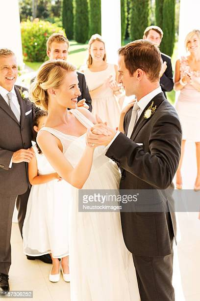 Newlywed Couple Looking At Each While Dancing During Reception