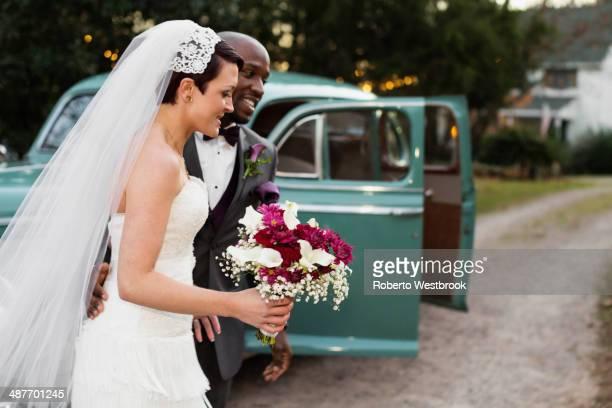 Newlywed couple outside vintage car