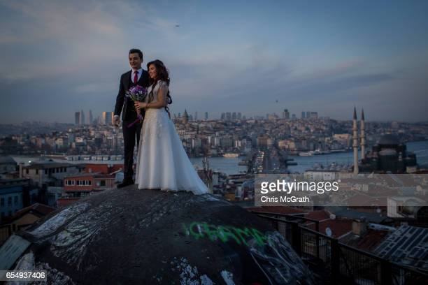 A newlywed couple pose for photographs on a rooftop of an old Istanbul Han overlooking the Bosphorus strait on March 18 2017 in Istanbul Turkey...