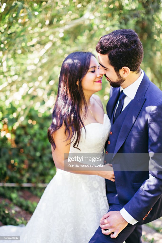newlywed couple romancing while standing at park stock photo getty