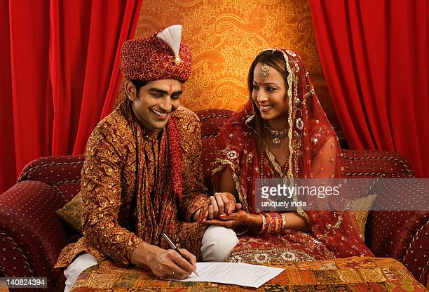 Newlywed couple signing a marriage certificate