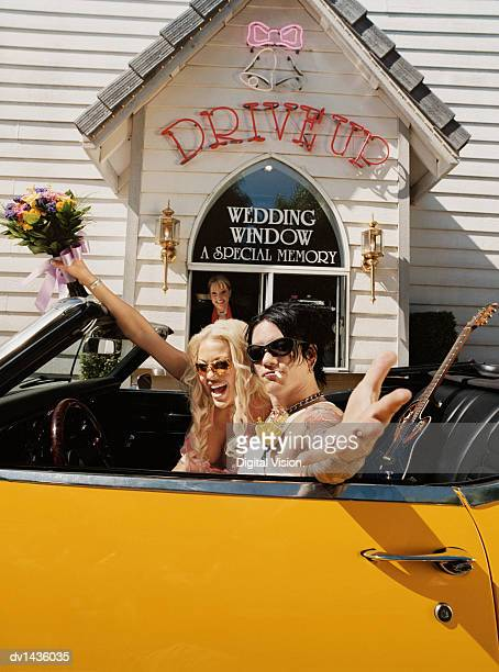 Newlywed Couple Sitting in a Yellow Convertible in Front of a Wedding Chapel