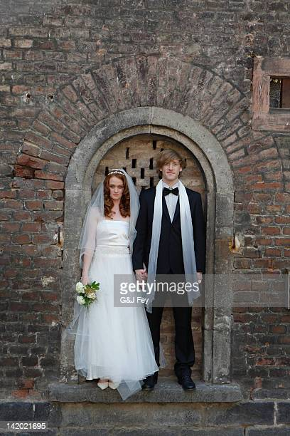 Newlywed couple standing in arch