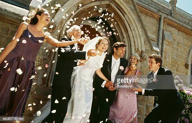 newlywed couple standing outside a church with their parents and guests