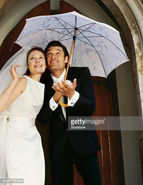 newlywed couple standing under an umbrella