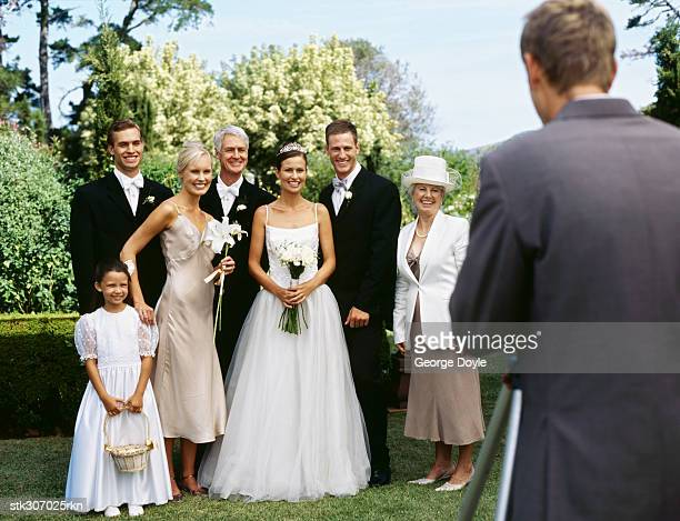 newlywed couple standing with their parents and guests and posing in front of a camera