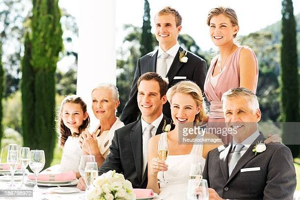 Newlywed Couple With Family And Wedding Guests At Reception