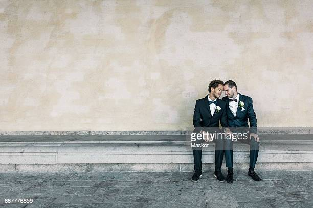 Newlywed gay couple sitting on bench against wall