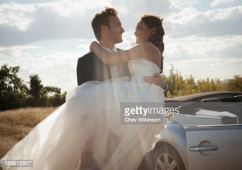Newlywed groom carrying bride outdoors