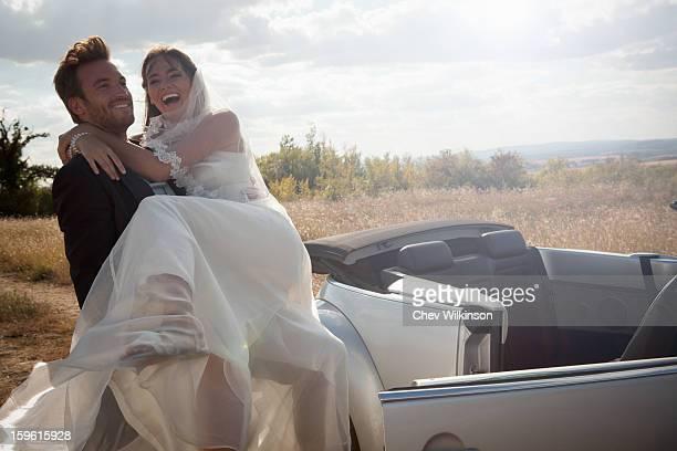 Newlywed groom carrying bride outdoors