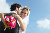 Newlywed Groom Kisses a Bride Holding a Bouquet on Her Cheek
