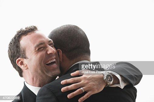 Newlywed grooms hugging outdoors