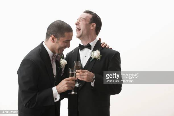 Newlywed grooms toasting each other