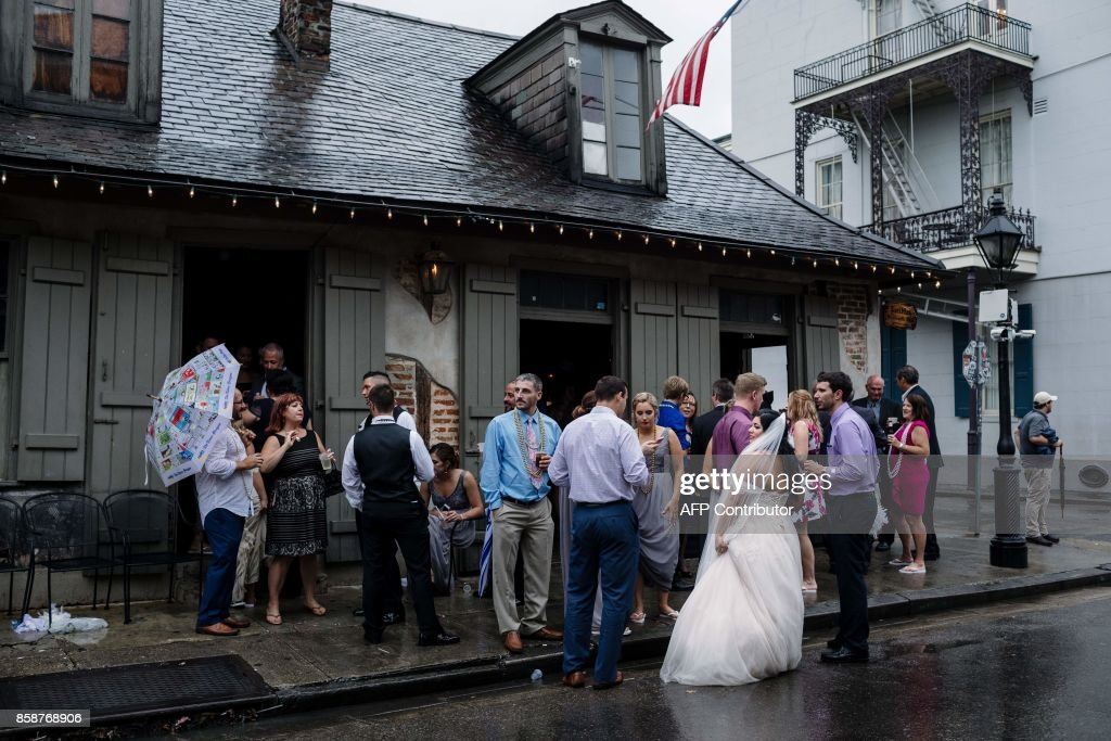 Newlywed Kaila Hager visits Lafitte's Blacksmith Bar with her wedding party after her wedding was moved from 7pm to Noon on account for the arrival of Hurricane Nate in New Orleans on October 7, 2017. Residents in three states along the US Gulf Coast scrambled to complete preparations Saturday ahead of Hurricane Nate as officials warned conditions would turn treacherous after sunset. Nate was forecast to arrive late Saturday as a Category Two hurricane, packing winds topping 90 miles per hour as it churned in the Gulf of Mexico. The storm killed at least 28 people in Central America. PHOTO / Bryan Tarnowski