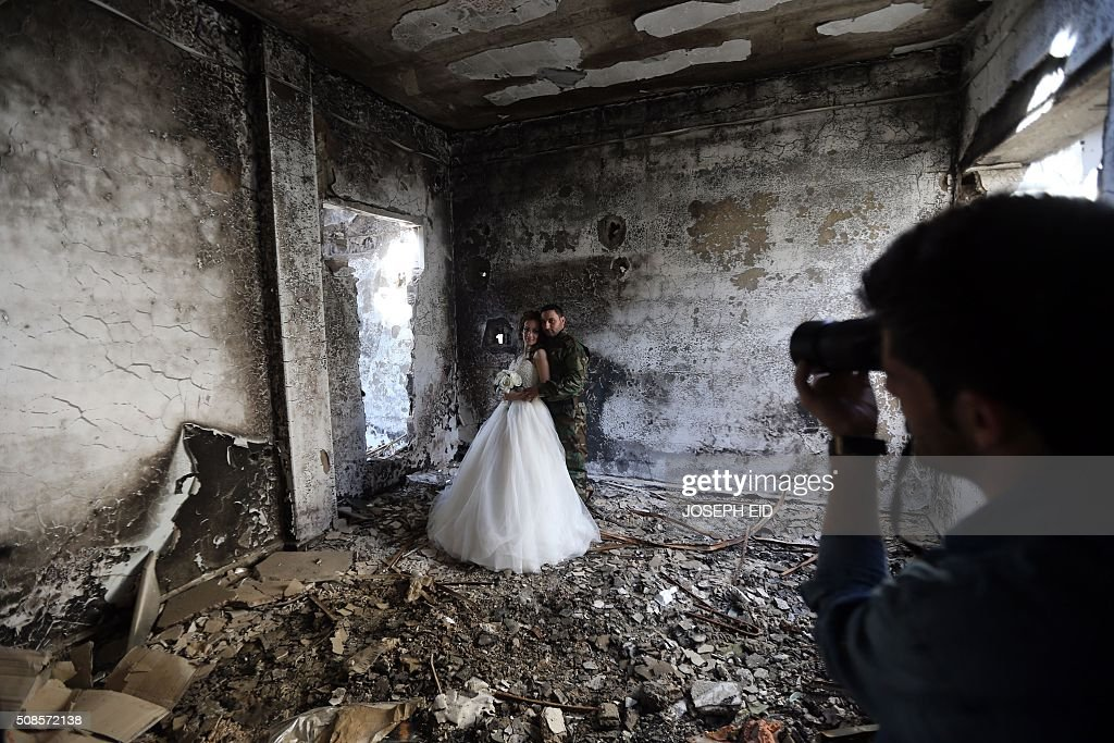 TOPSHOT Newlywed Syrian couple Nada Merhi and Hassan Youssef have their wedding pictures taken in a heavily damaged building in the war ravaged city...