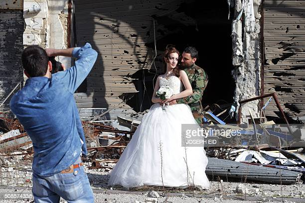 Newlywed Syrian couple Nada Merhi and Hassan Youssef have their wedding pictures taken in front of a heavily damaged building in the war ravaged city...