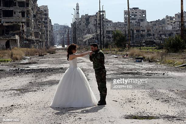 Newlywed Syrian couple Nada Merhi and Syrian army soldier Hassan Youssef pose for a wedding picture amid heavily damaged buildings in the war ravaged...