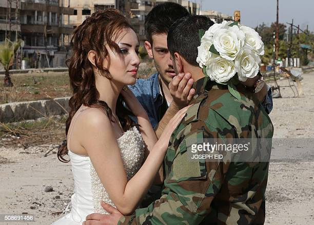 Newlywed Syrian couple Nada Merhi and Syrian army soldier Hassan Youssef receive instructions from their wedding photographer as they have their...