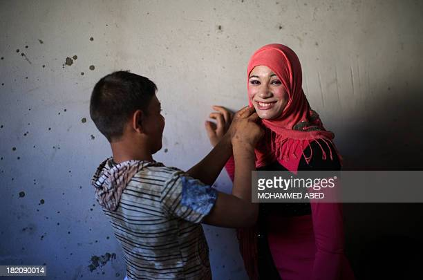 Newlywed Tala has her headscarf adjusted by her 15yearold husband Ahmed Soboh at their home four days after their wedding in the northern Gaza Strip...