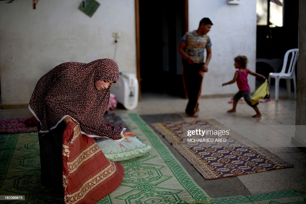 Newlywed Tala, 14, puffs a cushion as her 15-year-old husband Ahmed Soboh, is seen in the background at their home four days after their wedding in the northern Gaza Strip town of Beit Lahia, near the border with Israel on September 28, 2013. The young couple live in the family's three-room home, sharing it with nine other relatives. Ahmed works with his father as a road cleaner earning $5 (US dollars) per day.