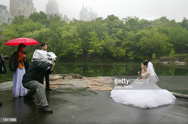 Newlywed Tina Moeing braves a drizzling rain as she poses for a videographer in Central Park May 13 2002 in New York City A storm system moving...