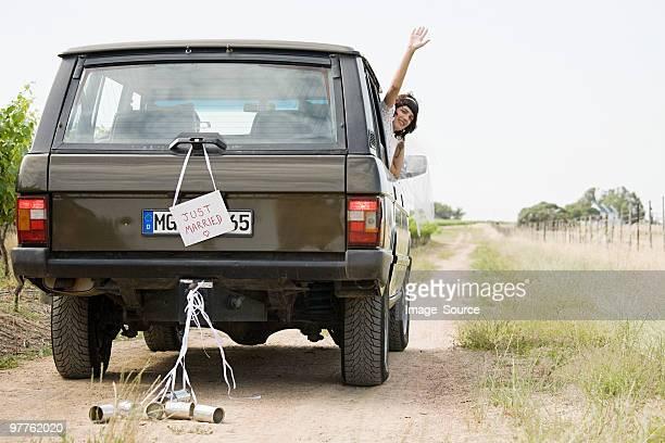 Frisch verheiratet Frau winkt vom Fahrzeug