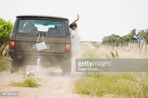 Newlywed woman waving from vehicle