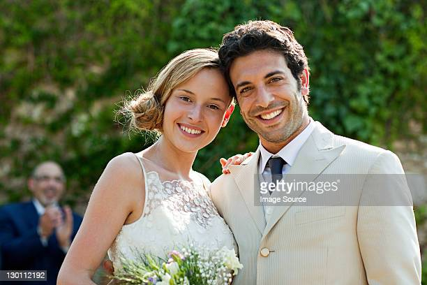 Newlyweds at marriage ceremony, looking at camera