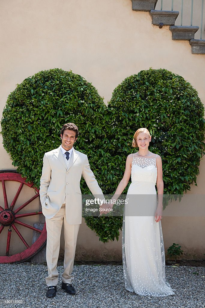 Newlyweds by heart shaped bush holding hands