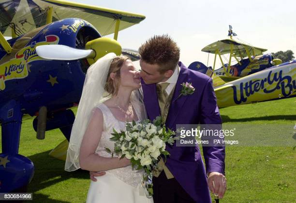 Newlyweds Caroline Hackwood and Justin Bunn seal with a kiss their wedding vows taken on the wings of 1940's Boeing Stearman biplanes in Rendcomb...