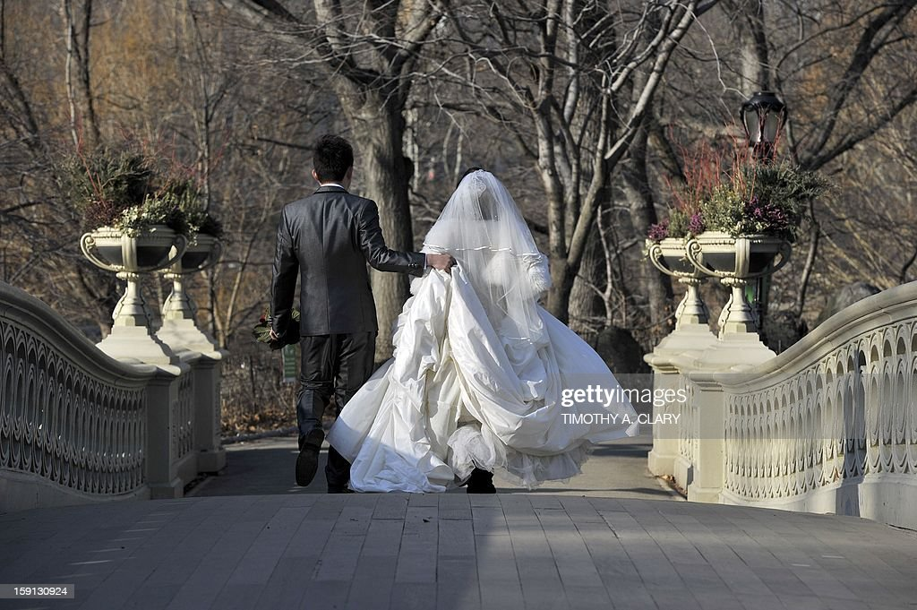 Newlyweds getting ready to pose for wedding photos cross the Bow Bridge in Central Park as New Yorkers and tourists take advantage of the unusually warm weather for winter in the city on January 8, 2013. Temperatures are expected to reach the upper 50's over the weekend.