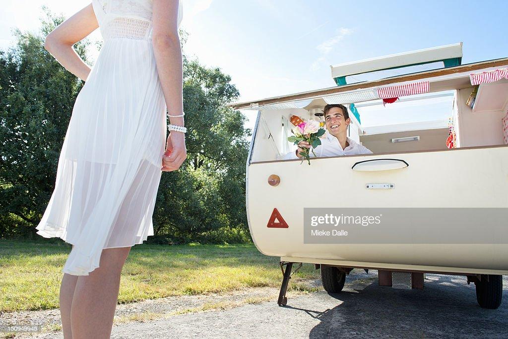 Newlyweds, groom in a retro caravan : Stock Photo