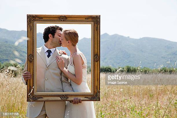 Newlyweds holding vintage picture frame, kissing