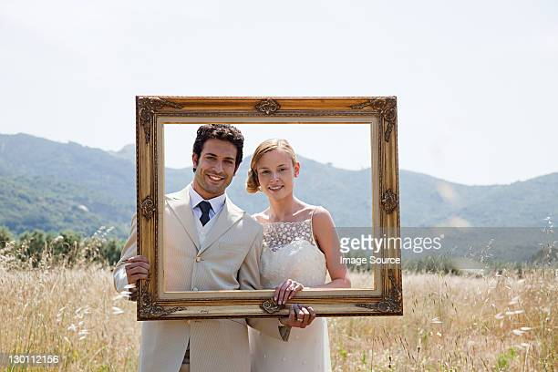 Newlyweds holding vintage picture frame