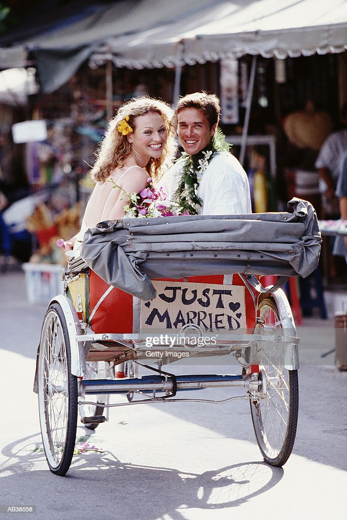 Newlyweds in cycle carriage with 'just married' sign on back : Stock Photo