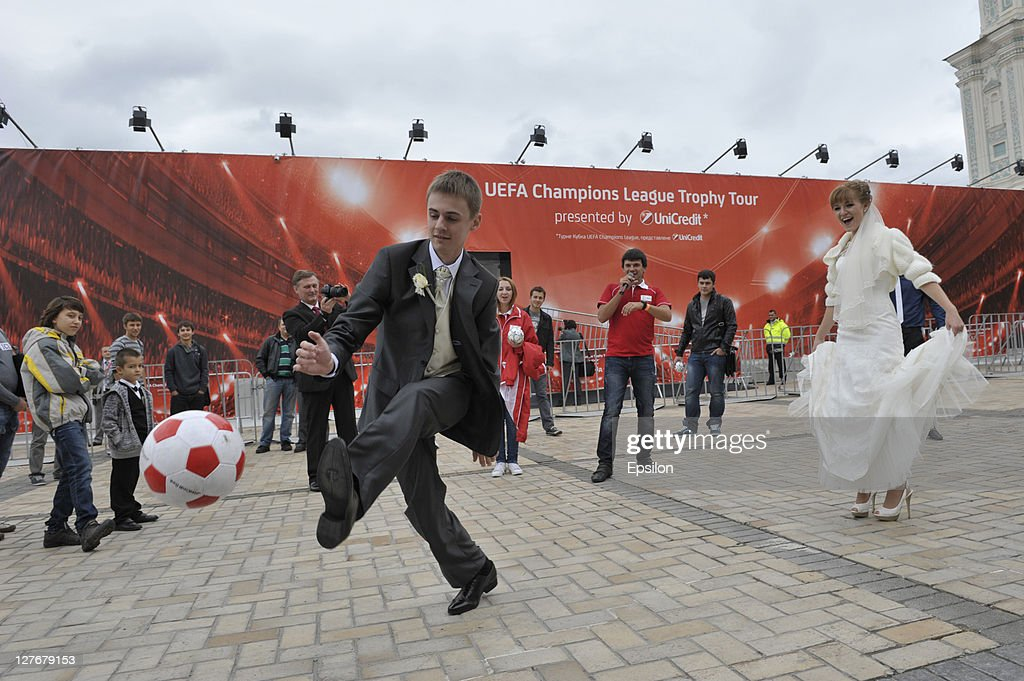 Newlyweds kick a ball during during a signing session for fans at the UEFA Champions League Trophy Tour 2011 on September 30, 2011 in Kiev, Ukraine.