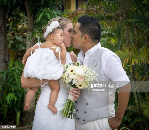 Newlyweds Kissing holding Baby Daughter