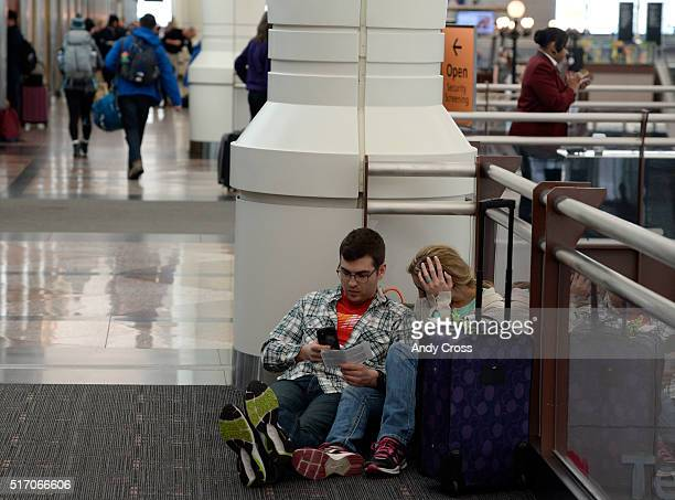 Newlyweds Peter Aukstolis and Laura Hargadine try to get flight info on their honeymoon trip to Aruba at Denver International Airport March 23 2016...