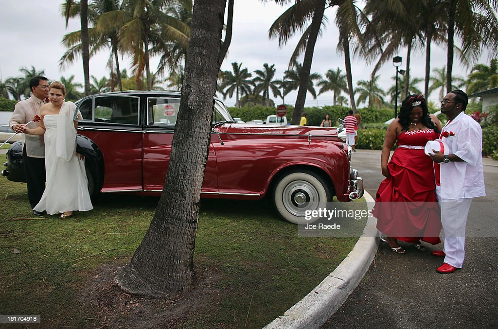 Newlyweds Rem David (L) and Jenny Briceno (2nd L) and Karean Butler (2nd R) and Karlo Butler walk near a Rolls-Royce after taking part in a group Valentine's day wedding at the National Croquet Center on February 14, 2013 in West Palm Beach, Florida. The group wedding ceremony is put on by the Palm Beach Country Clerk & Comptroller's office and approximately 40 couples to tied the knot.