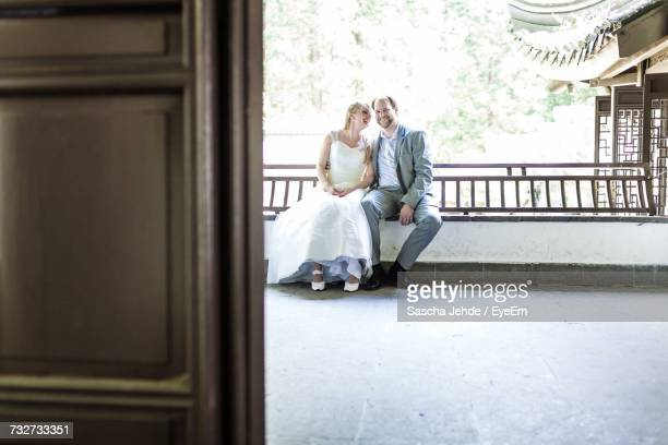 Newlyweds Sitting Outdoors