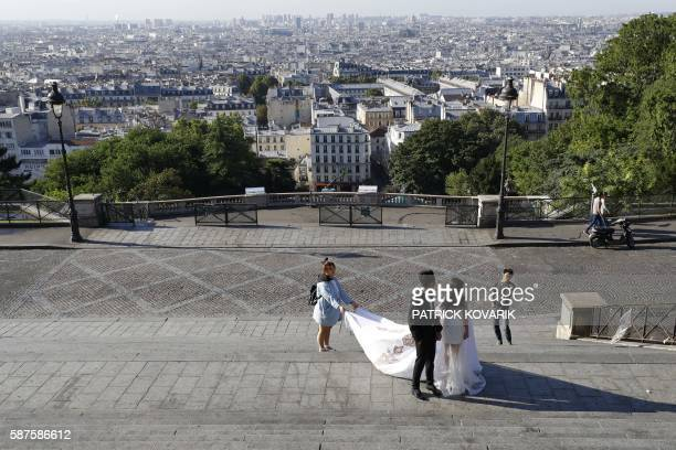 Newlyweds stand on deserted steps near the SacreCoeur Basilica in the Montmartre neighborhood in Paris on August 9 2016 Many places and events in...