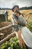 Newlyweds stand, smile and hug during honeymoon trip on background of old wooden hut and fence in Carpathian mountains. Closeup.