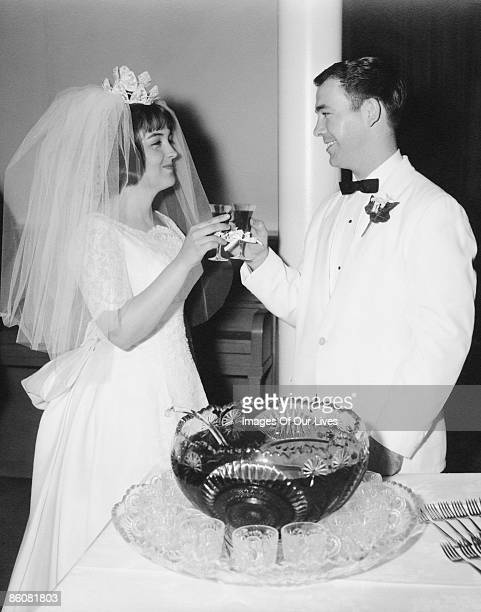 Newlyweds toasting by punch bowl