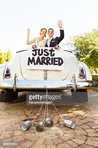 Newlyweds Waving In Convertible Car With Cans Attached To It