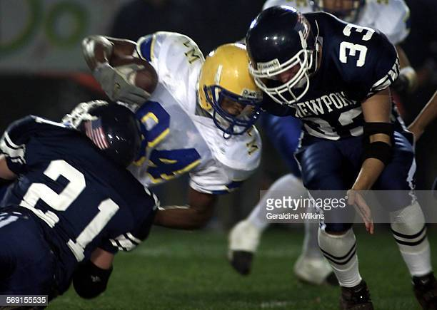 Newport Harbor players @@ 21 Tyler Miller and @@ 33 Cory Ray tackle La Mirada player @@ 84 Jarrell Shavers in the first period in the southern...