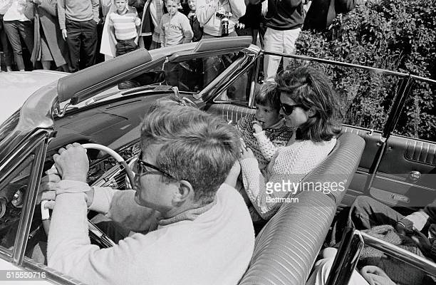 John Jr has his finger in his mouth while sitting on his mothers' lap as President Kennedy drives an open car leaving Bailey's Beach in Newport for a...