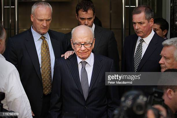 News Corp Chairman Rupert Murdoch looks down as he leaves the One Aldwych Hotel surrounded by his personal security team to speak with reporters...