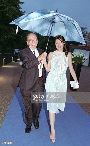 News Corporation Chairman and CEO Rupert Murdoch shelters his wife Wendi from the rain as they leave Mr Murdoch's annual Summer Party which was held...